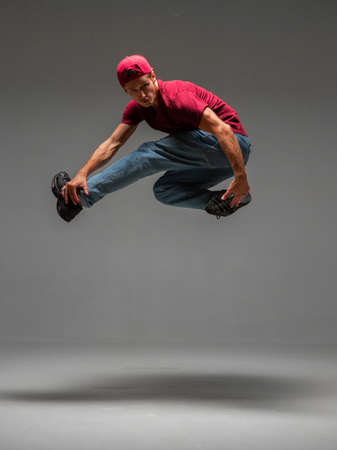 Cool young guy breakdancer jumps dancing hip-hop isolated on gray background. Dance school poster. Break dance lessons Stok Fotoğraf