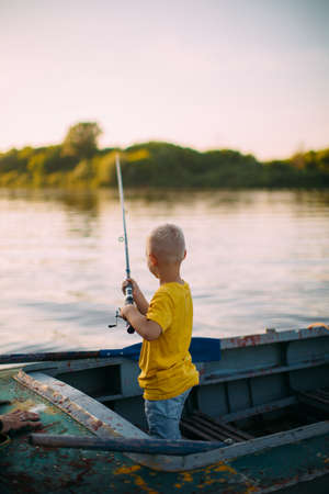 Baby boy fishing from boat on river in summertime, back view Stockfoto