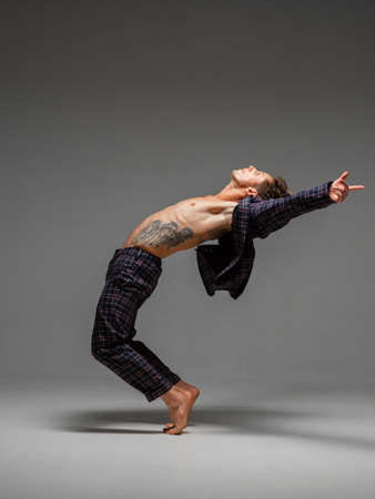 Handsome flexible guy dancing expressive dance in suit with naked torso isolated on gray background. Body with tattoo