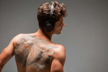 Cool young guy in wireless headphone listen to song with naked back isolated on gray background. Body with tattoo