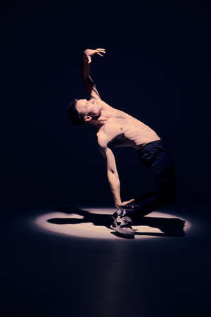 Cool young guy dancer with naked torso dancing in studio in spotlight on black background. Dance school poster