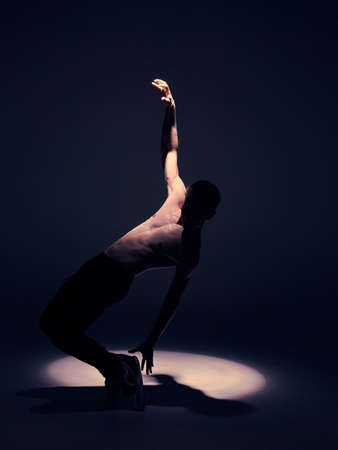 Cool young guy dancer with torso dancing in studio in spotlight on black background. Dance school poster