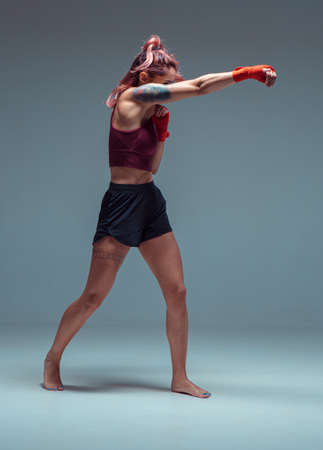 Sporty woman fighter trains in boxing bandages in studio isolateed on gray background. Mixed martial arts poster
