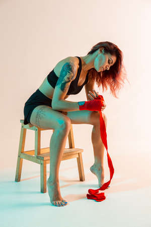Beautiful female fighter putting on boxing bandages in studio in neon light. Mixed martial arts poster