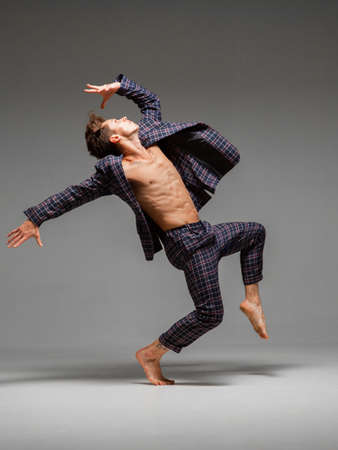 Stylish young guy breakdancer in suit with torso and barefoot dancing in studio isolated on gray background