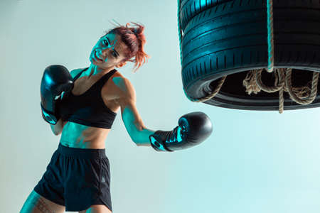 Athletic female fighter trains uppercut on punching bag made of tires in studio in neon light. Mixed martial arts poster