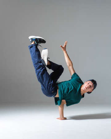 Cool b-boy dancing breakdance on the floor in studio isolated on gray background. Breakdancing school poster