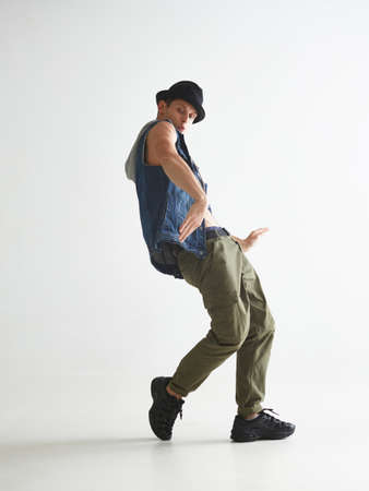Stylish young guy breakdancer in hat dancing hip-hop in studio isolated on white background. Break dance lessons