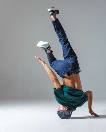 Cool guy breakdancer dancing on one hand isolated on gray background. Breakdance poster