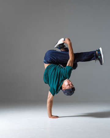 Cool guy breakdancer dance on the floor standing on one hand isolated on gray background. Breakdance lessons