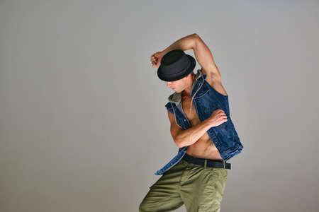 Young guy breakdancer in hat dancing hip-hop in studio isolated on gray background. Dance school poster