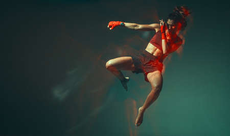 Cool female fighter jumping levitating in neon light in stylish sportswear. Womens sport concept. Long exposure shot