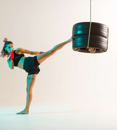 Cool girl in stylish sportswear kicking with punching bag isolated in neon light. Womens sport and motivation concept