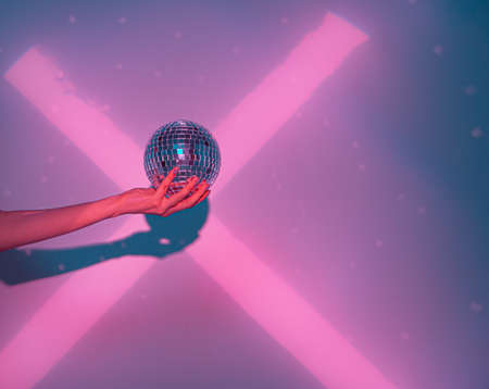 Close up of disco ball in female hand in cross shaped pink neon light in studio. Trendy poster to announce party Stock fotó
