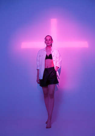 Fashionable young girl standing in violet neon light with pink cross in studio. Trendy poster for club party 免版税图像