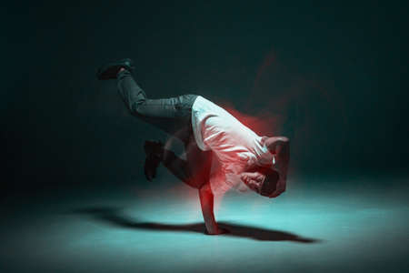 Stylish young guy breakdancer dancing hip-hop in neon light. Long exposure shot. Battle competition announcement