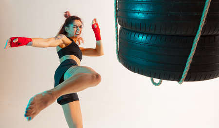 Cool female fighter trains kicking with punching bag made of tires in neon studio light. Womens sport workout