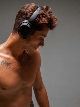 Portrait of stylish young man in wireless headphone listening to song with naked torso on gray background. Music poster