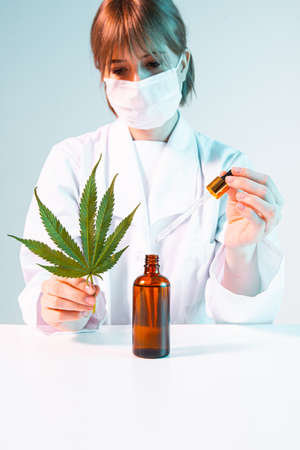 Female scientist with a cannabis leaf, pipette and a bottle of cannabis oil developing hemp products