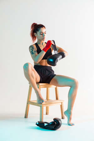 A young boxer girl with red bandages on her hands poses on a chair in a photo Studio.