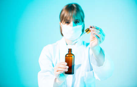 Female young doctor with glass jar of serum and pipette in hands in neon blue light