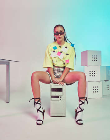 Stylish young female office worker with stickers on t-shirt sitting on system unit. Colored Neon light