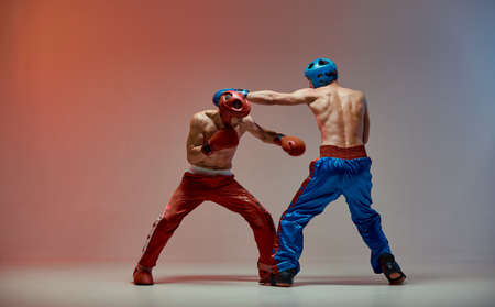 Jab of fighting males in boxing gloves with fit torsos in red light in studio, martial arts, mixed fight concept