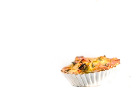 French leek quiche with ham and wild rocket on the white background