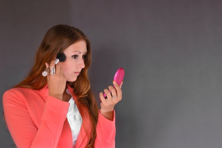 Young successful businesswoman wearing an office clothes using make up  Isolated on the grey bacground