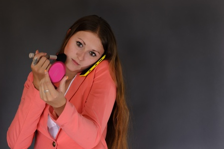 celphone: Young successful businesswoman wearing an office clothes using make up and phone  Isolated on the grey bacground