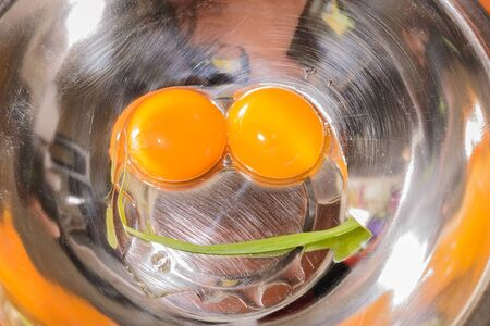 Two eggs in the metalic bowl with the small onion bulb - Like smile  Stock Photo