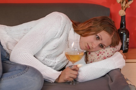 Depressed woman lying on the sofa with the glass of wine