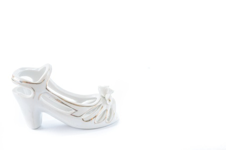 Porcelain light shoe with gold bordering on the white background  Stock Photo