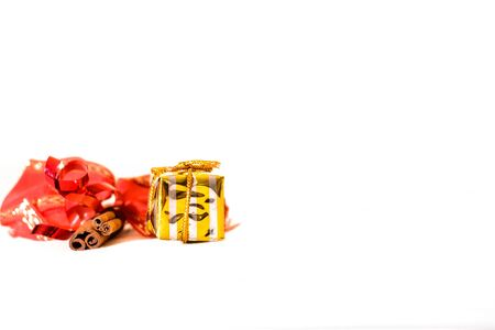 Yellow Christmas box with cinnamon  and red ribbon on white backgound  Stock Photo