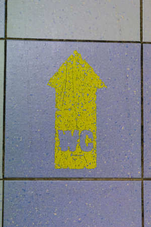 Yellow WC Arrow Sign on the floor background  photo