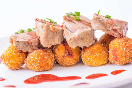 Detail of Home meda Delicious roast pork with currant sauce and home made croquette. Stock Photo