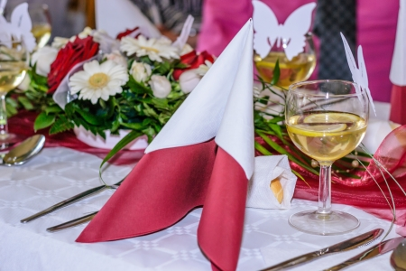 Beautiful red style wedding table with wine and napkins and decoration