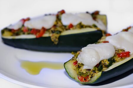 Detail of home made Stuffed zucchini, courgette halves with mozzarella cheese isolated on white background  Stock Photo