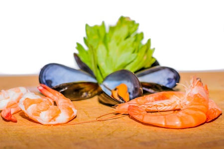 Detail of Sea food - shrimp, mussel, ink-well  with green decoration on white background. Stock Photo