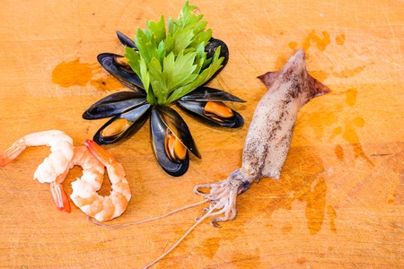 Detail of Sea food - shrimp, mussel, ink-well  with green decoration on chopping board.