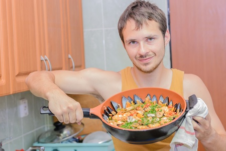 Young man cooking paella - Spanish food, in the kitchen  photo