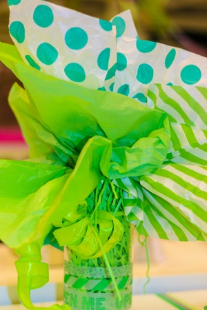 Gift flower with green ribbon decoration. Polka dot style. photo