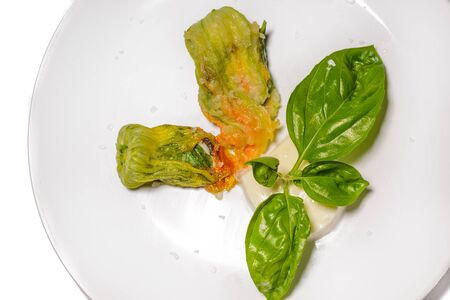 Detail of Fried stuffed zucchini flower on a plate. Stock Photo