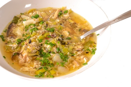 Tasty bouillon with home made nudles on the white background.