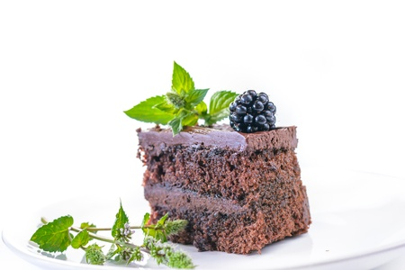 Detail of home made chocolate cake with blackberry and mint on white background.
