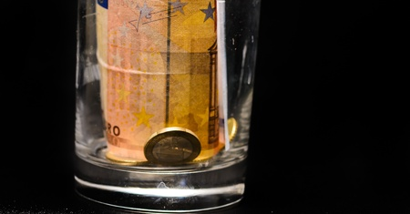 Money in a glass jar on a white background - money savings or tips