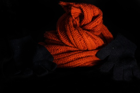 Winter orange scarf with black gloves on black background