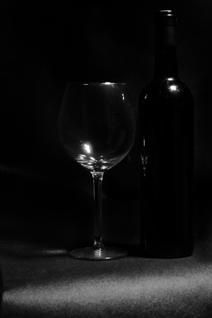 Detail of wine glass and bottle on black backround. photo