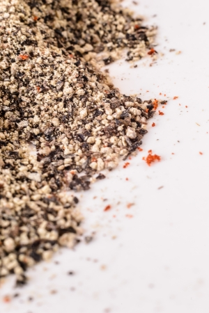 Detail of heap black pepper on the white. Stock Photo