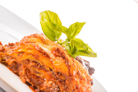 Detail of delicious food lasagne bolognese, close up, creative food with basil. White background.
